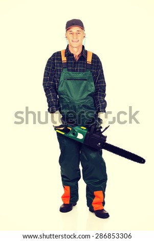 Mature sawyer in workwear holding a chainsaw. - stock photo