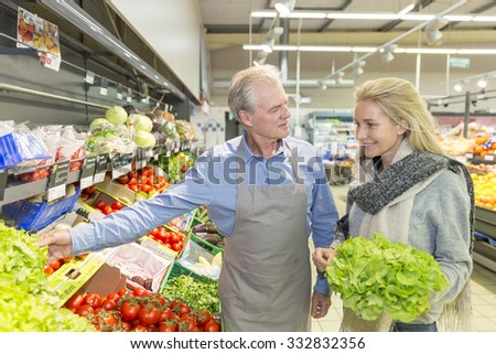 Mature seller in supermarket with client