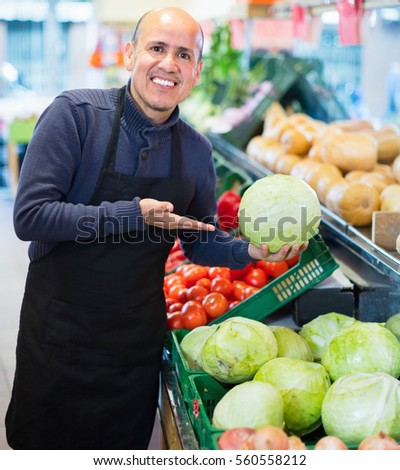Mature seller offering seasonal vegetables in local grocery