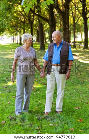 mature senior couple in love. walking in a meadow - stock photo