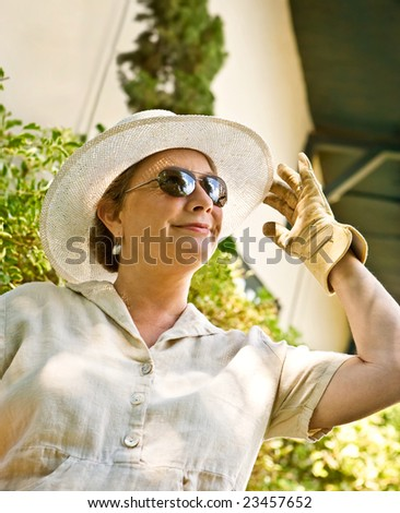 Mature, senior woman in sunhat and gardening gloves greeting the sunny day with enthusiasm - stock photo
