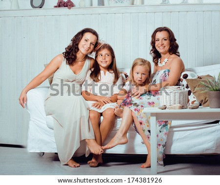 Mature sisters twins at home with little daughter, happy family - stock photo