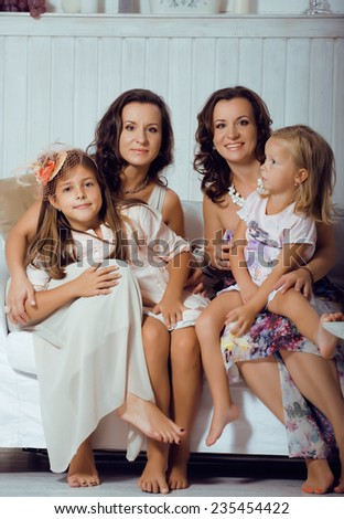 Mature sisters twins at home with little daughter, happy family in interior - stock photo