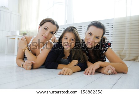 mature sisters twins at home with little daughter, happy family in interior close up - stock photo