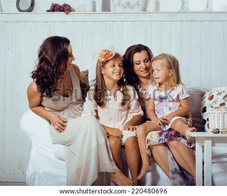 Mature sisters twins at home with little daughter, happy family smiling - stock photo