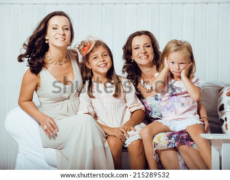 Mature sisters twins at home with little daughter, happy real family - stock photo