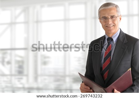Mature smiling business manager holding a folder while standing in front of a large office window. Horizontal format with copy space. - stock photo