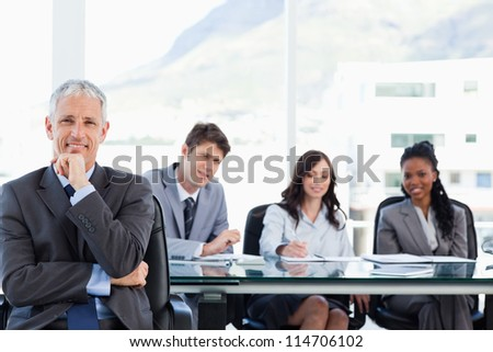 Mature smiling manager sitting with his hand on his chin while his team is looking at him - stock photo