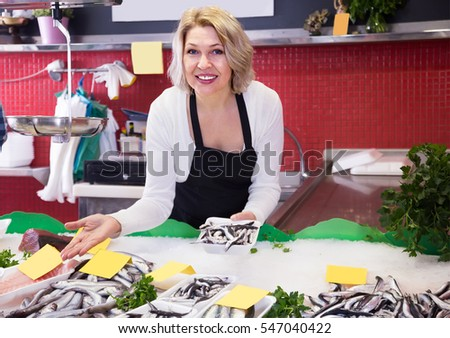 Mature smiling sales woman working at counter in fish store