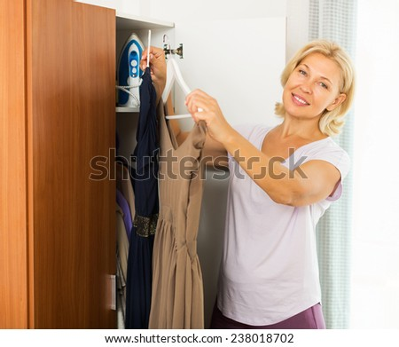 Mature smiling woman at wardrobe. She thinking what get dressed - stock photo