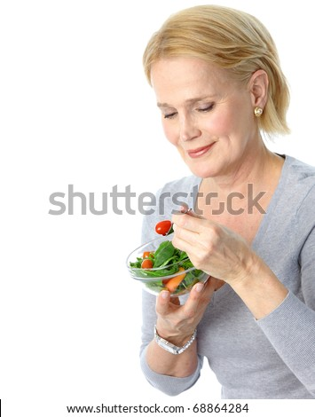 Mature smiling woman  eating salad,  fruits and vegetables. - stock photo