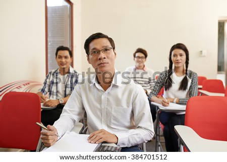 Mature student listening to the lecturer with interest