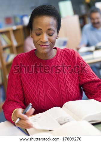 Mature student studying in library - stock photo