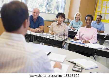 Mature students and their teacher in a classroom - stock photo