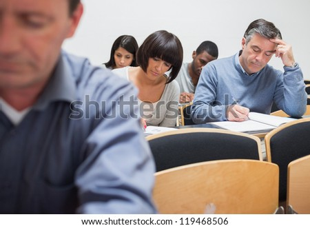 Mature students in lecture in college - stock photo