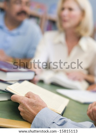 Mature students studying in library, focus on hands holding book in foreground