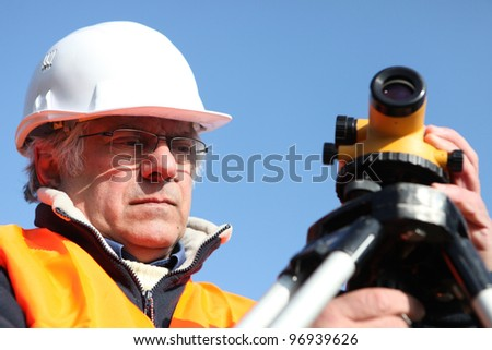 mature surveyor in construction site - stock photo