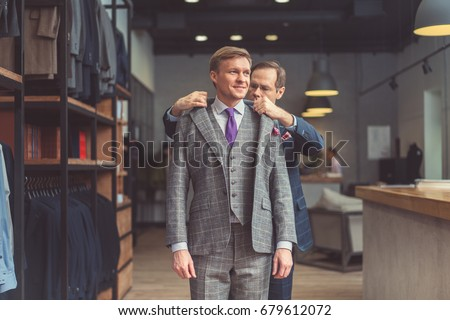 Mature tailor and customer in atelier