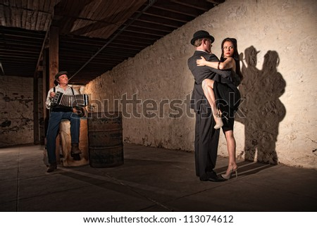 Mature tango dancers under spotlight with bandoneon player - stock photo