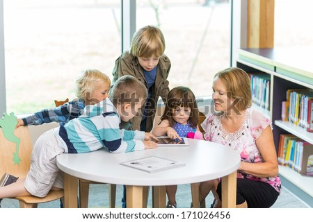 Mature teacher with students using digital tablet at table in school library - stock photo