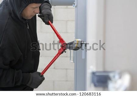 Mature thief breaking lock to open the door - stock photo