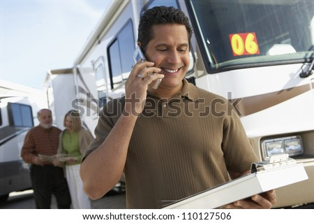 Mature tourist guide talking on phone while holding a book with passengers in background - stock photo