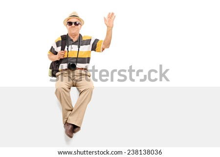 Mature tourist waving with his hand seated on a billboard isolated on white background - stock photo