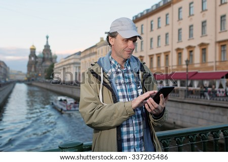 Mature tourist with a tablet in St. Petersburg, Russia - stock photo