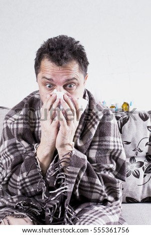 Mature unshaven sick man wrapped in a blanket wipes his nose with a tissue. Behind are drugs.
