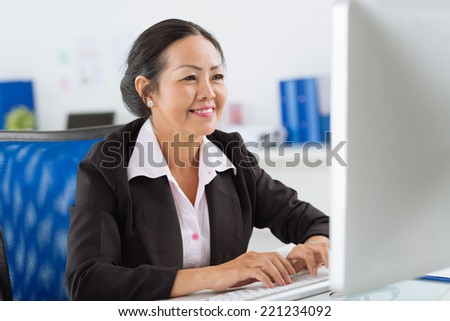 Mature Vietnamese manager working on the computer - stock photo