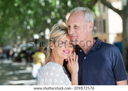 Mature wife cuddling up to old husband in the street looking very happy - stock photo