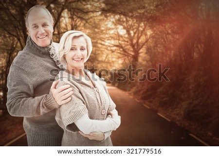 Mature winter couple against country road - stock photo