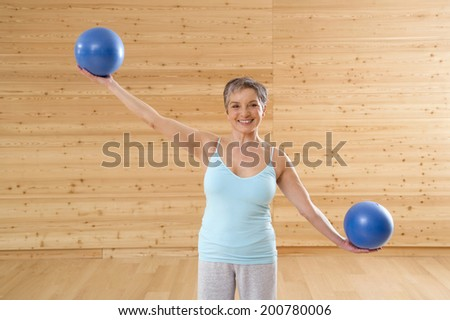 Mature woman balancing with rubber balls