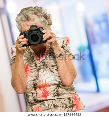 Mature Woman Capturing Photo, Indoors - stock photo