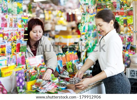 mature woman chooses solid fertilizer  at store for gardeners - stock photo