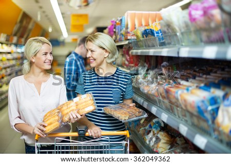 Mature woman choosing pastry in bakery section of supermarket  - stock photo