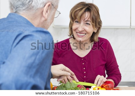 Mature woman  chopping  vegetable and looking at her husband. - stock photo
