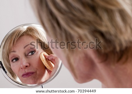 Mature Woman Cleaning Face - stock photo