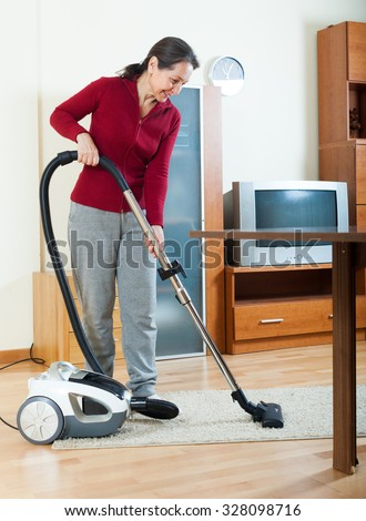 Mature woman cleaning living room