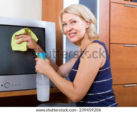 mature woman  cleaning  screen of TV with cleanser at home