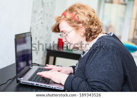 Mature woman close-up looking and typing on laptop keyboard - stock photo