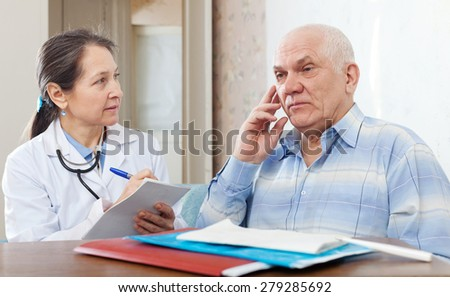 Mature woman doctor examining the senior patient in clinic - stock photo