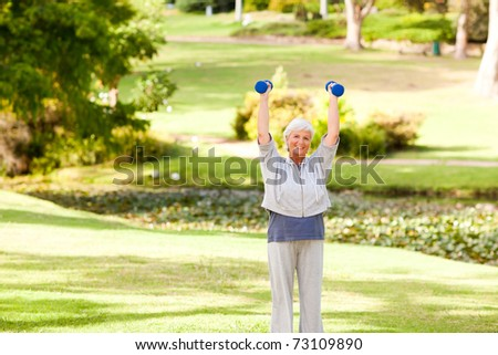 Mature woman doing her exercises in the park - stock photo