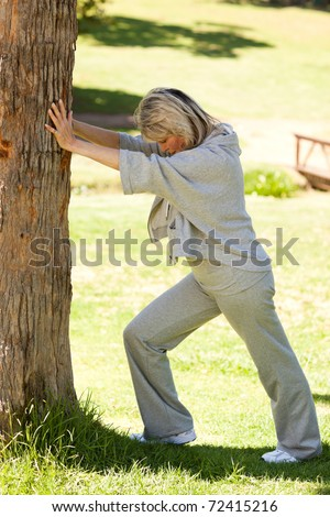 Mature woman doing her streches in the park - stock photo