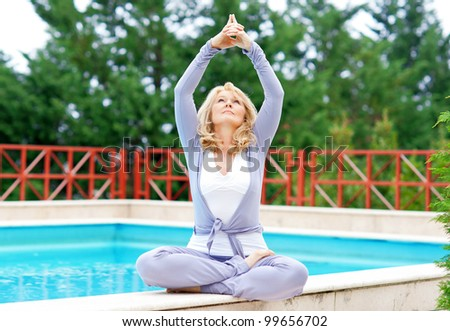 mature woman doing lotus yoga position in front of the pool
