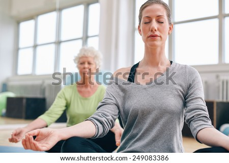 Mature woman doing yoga with senior female in background. Women sitting in lotus pose while mediating in yoga class - stock photo