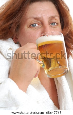 Mature woman drinking beer in sauna. Isolated over white.