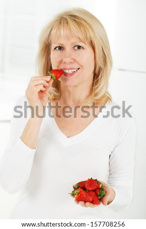 Mature Woman Eating A Bowl Of Strawberries and smiling - stock photo