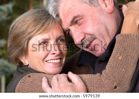 Mature woman embraces her husband. - stock photo