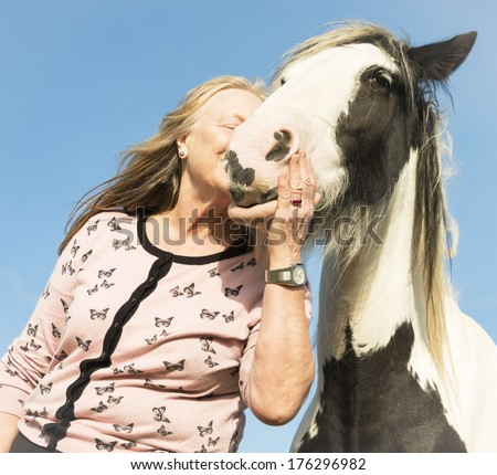 mature woman embracing and kissing her horse - stock photo